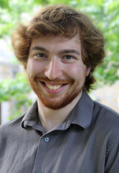 Person with auburn hair and facial hair wearing a grey shirt smiles with green leaves in the background
