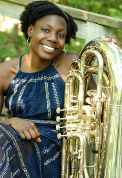 A black woman with short black hair wearing a blue patterned dress smiles while holding a tuba outdoors