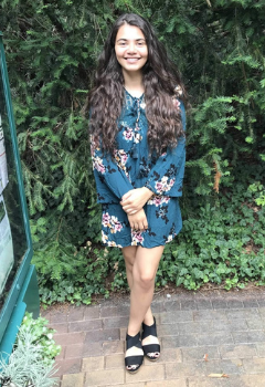 A person will long brown hair wearing a teal floral dress and black open toed shoes smiles before a background of greenery