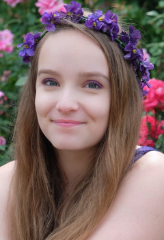 A person with long light brown hair wears a crown of purple flowers and grins in front of a flowering bush with pink flowers