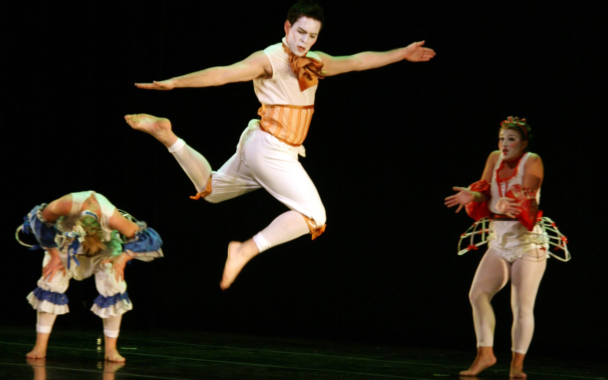 three people in costume on stage dancing, on in midair
