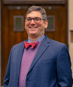 Stephen DiBenedetto Stands Before Beaumont Tower Wearing Glasses and Smiling in a Blue Checked Jacket Purple Sweater and Red Bowtie