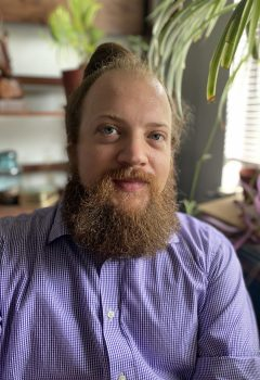 Man with blond beard and blue eyes, wearing a purple and white gingham button down, collared shirt sits with plants and shelving in the background