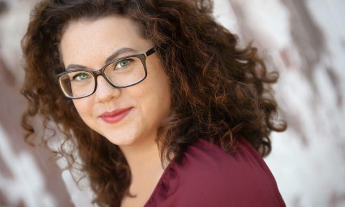 woman with brown curly hair and glasses